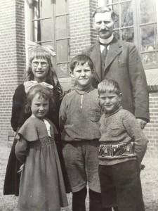 Vier van de kinderen Broekema met hun vader, de onderwijzer Thomas Broekema, voor de school in Hoogkerk. Links staan Aagtje (met bril) en Bonnie.
